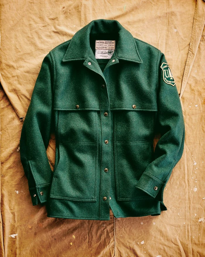 vintage green United States Forest Service and Filson jacket with department patch on brown canvas backdrop