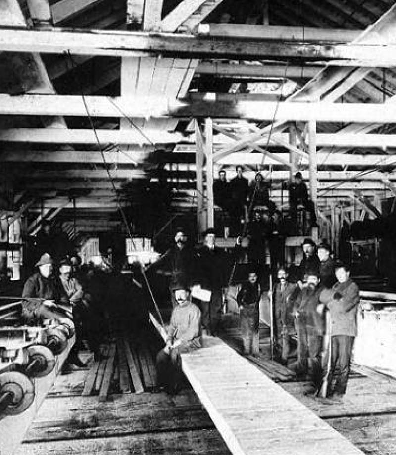 man sitting in saw mill for group photo
