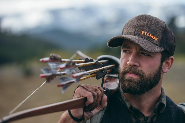a brunette, bearded man wearing a brown ball cap with orange text reading FILSON, wearing a backpack and holding a longbow with 4 arrows with the grey feathers facing forward
