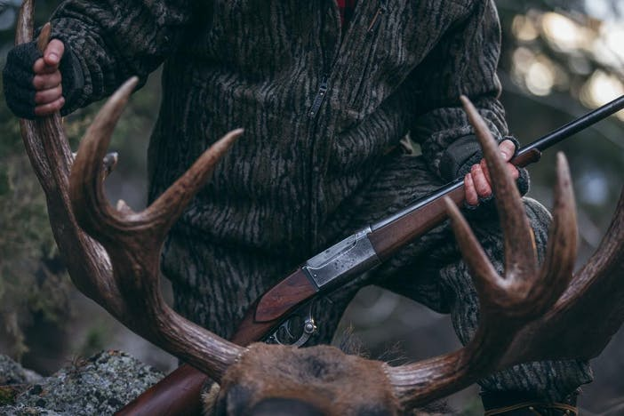 a hunter wearing a matching set of wool camo jacket and pants, holding a rifle kneeling over the rack of a killed moose