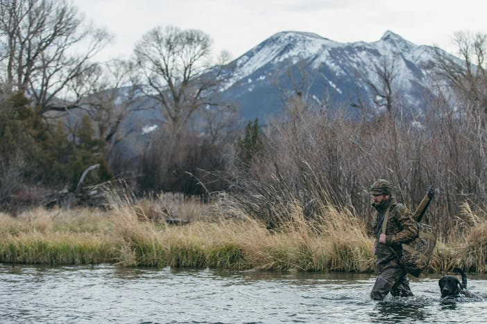 hunter wearing camo walking through river with his black lab alongside a grassy marsh and snowy mountain peaks in the background