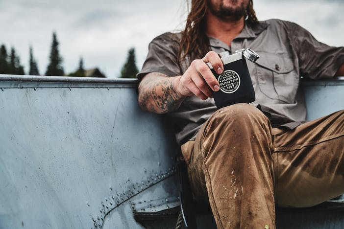 man wearing grey button up t-shirt, brown pants with tattoos holding an aluminum and black flask sitting in a metal canoe