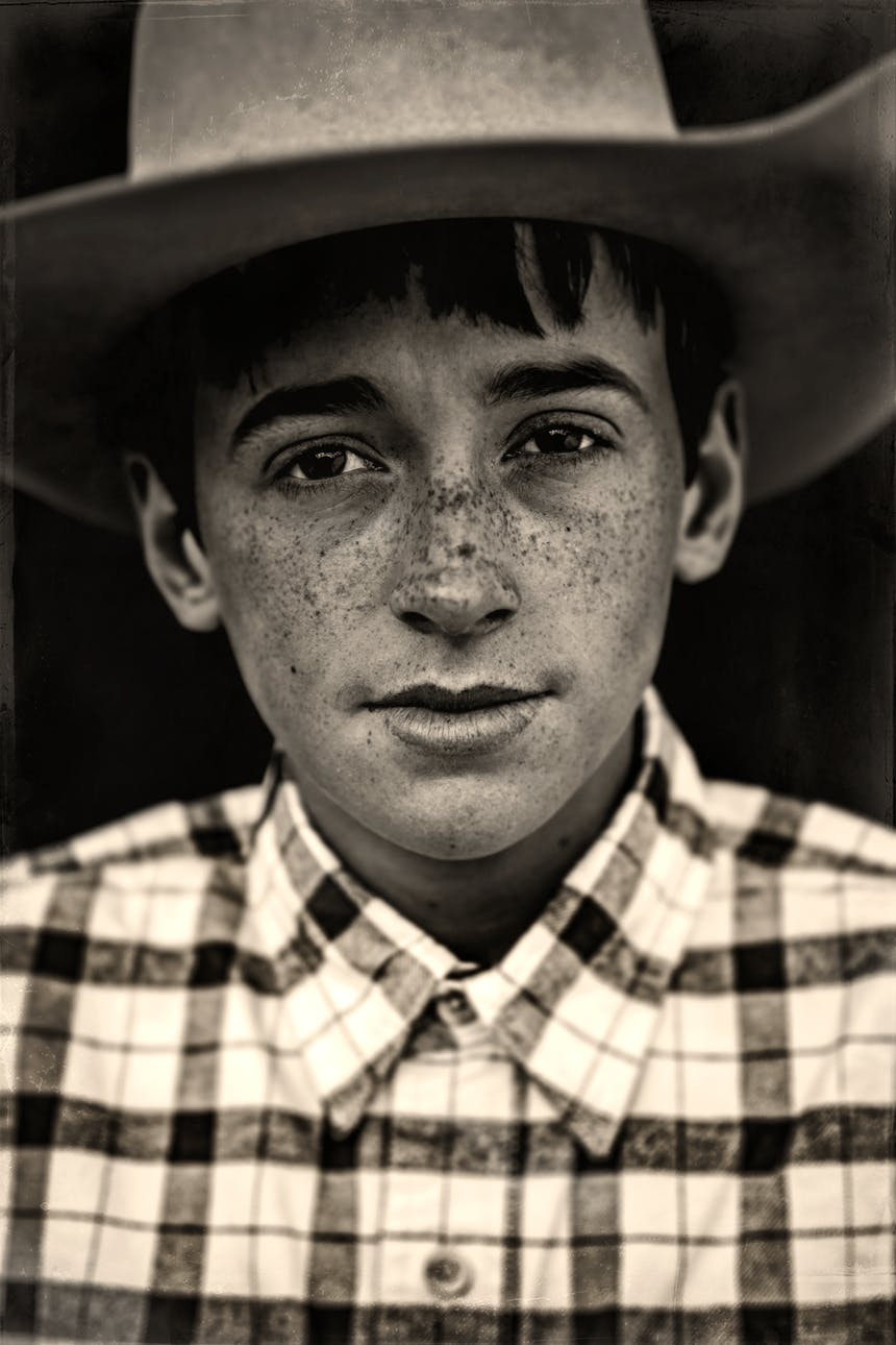 a black and white portrait image of a freckled face boy wearing a light colored cowboy hat and white and black plaid shirt buttoned to the top button