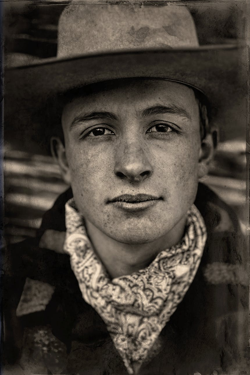 a black and white portrait image of a boy wearing a light colored cowboy hat, white and grey scarf and plaid jacket