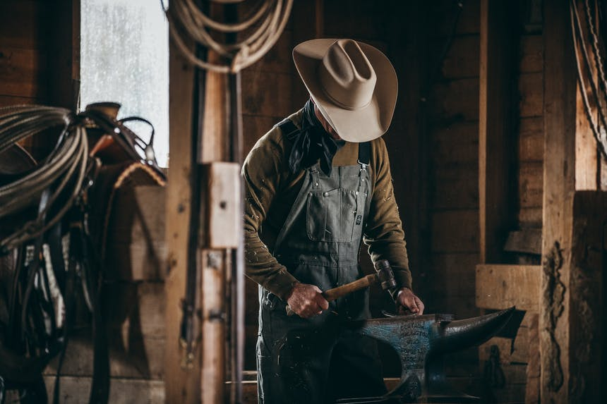 a man wearing black work overalls, a dark brown long sleeve and white cowboy hat looking down as he works on a horshoe in a barn