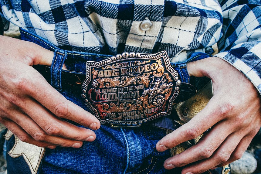 a close up of a boys gold and black rodeo belt buckle on his jeans with his white and black plaid flannel tucked in