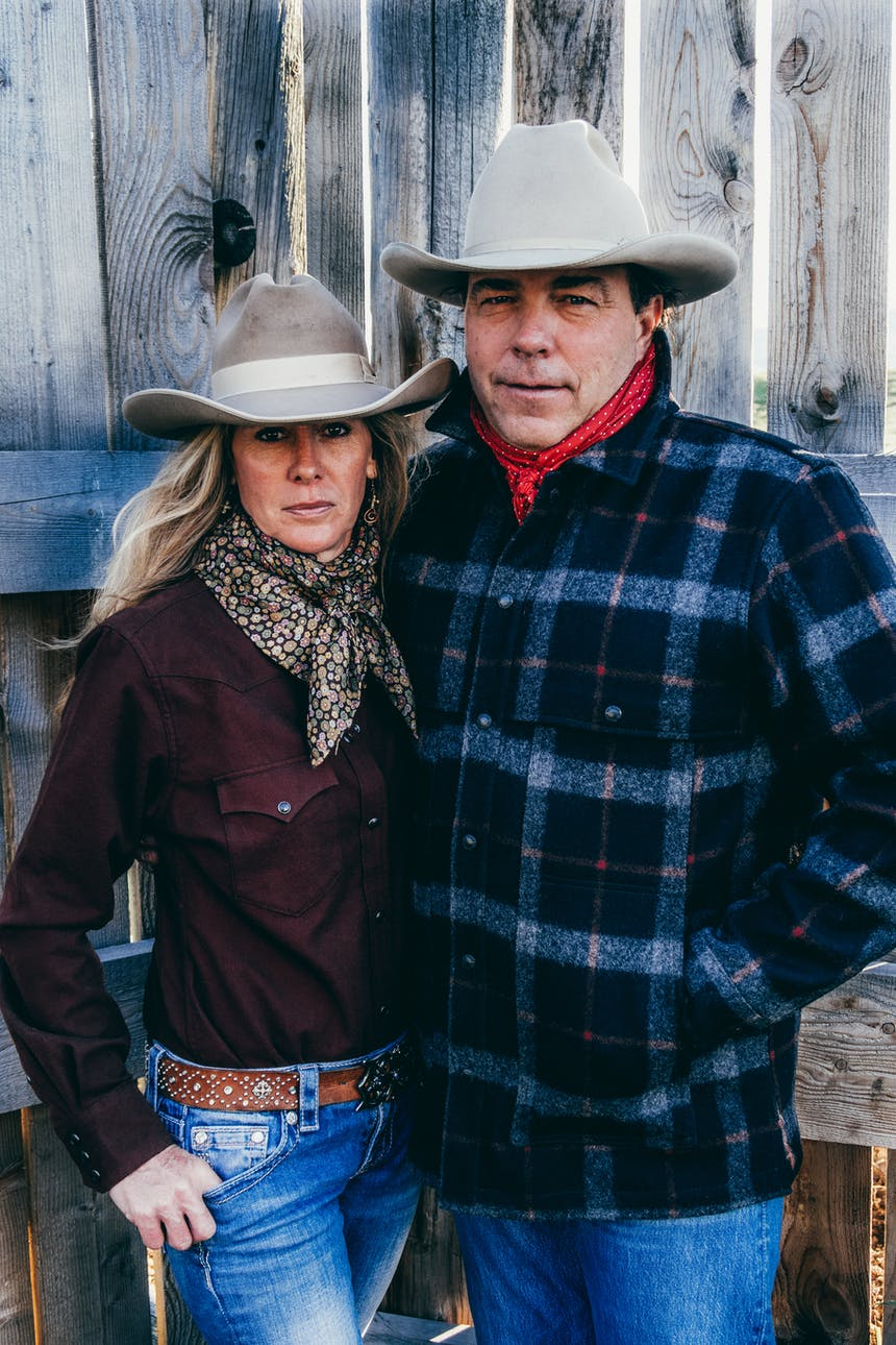 a blonde woman wearing a light brown cowboy hat, red long sleeve shirt, jeans, brown leather belt and brown scarf next to a dark haired man wearing a white cowboy hat, plaid black white and red jacket, jeans and red scarf in front of a wooden fence