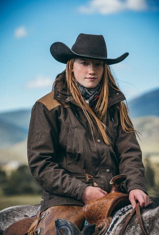 a long light brown haired girl sitting in a saddle onto of a brown horse wearing a black cowboy hat and brown jacket