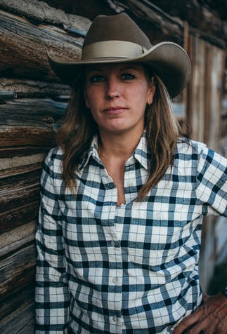 a women with long dirty blonde hair wearing a light brown cowboy hat and black and white flannel shirt standing next to a cabin