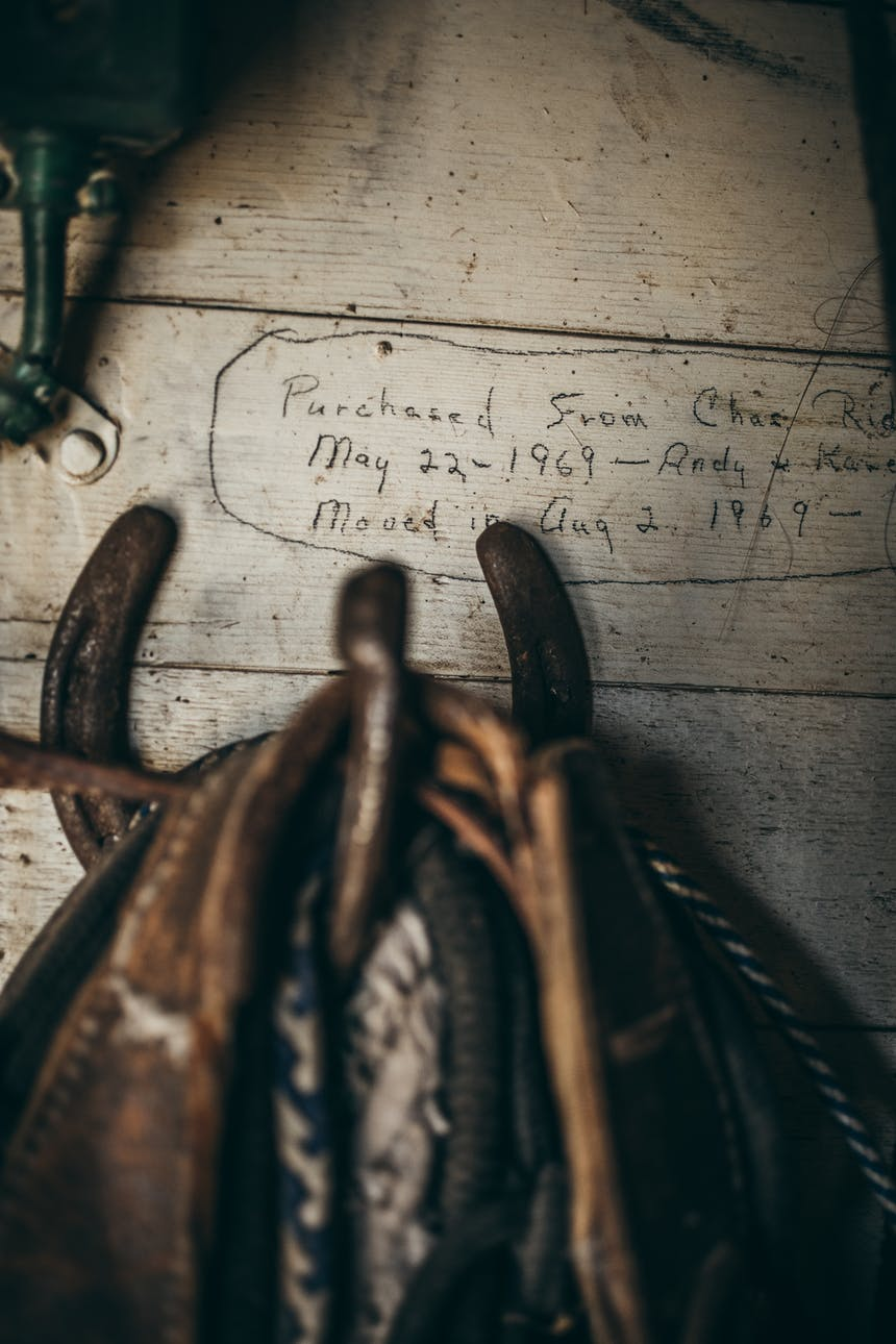 a close up of a horseshoe holding various ropes and guides for horses with text on the wooden barn board reading, purchased from Chas Riding May 22, 1969 - Andy and Kane moved in Aug 2, 1969