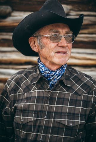 a portait image of an older man wearing a brown western flannel shirt, blue scarf and black cowboy hat wearing glasses and holding a toothpick in his teeth.