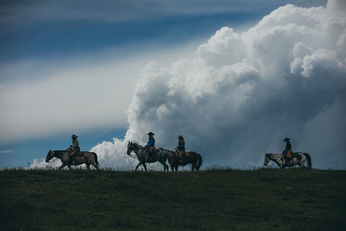 dark cloudy landscape with four horses and riders on the crest of a hill riding towards the left side of the image