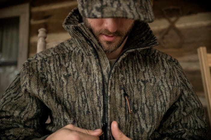 a close up of a hunter zipping up his camo jacket wearing a camo ball cap standing outside of a cabin
