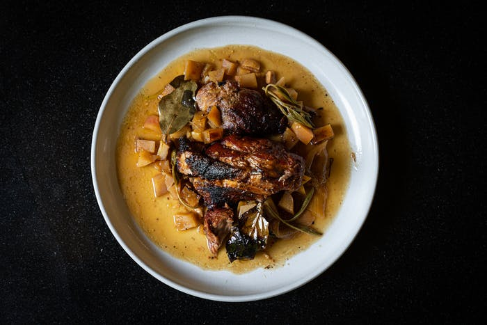 a white plate sitting on a black countertop plated with a cut of cooked pork butt, diced potatoes and a few springs of sage and a bay leaf