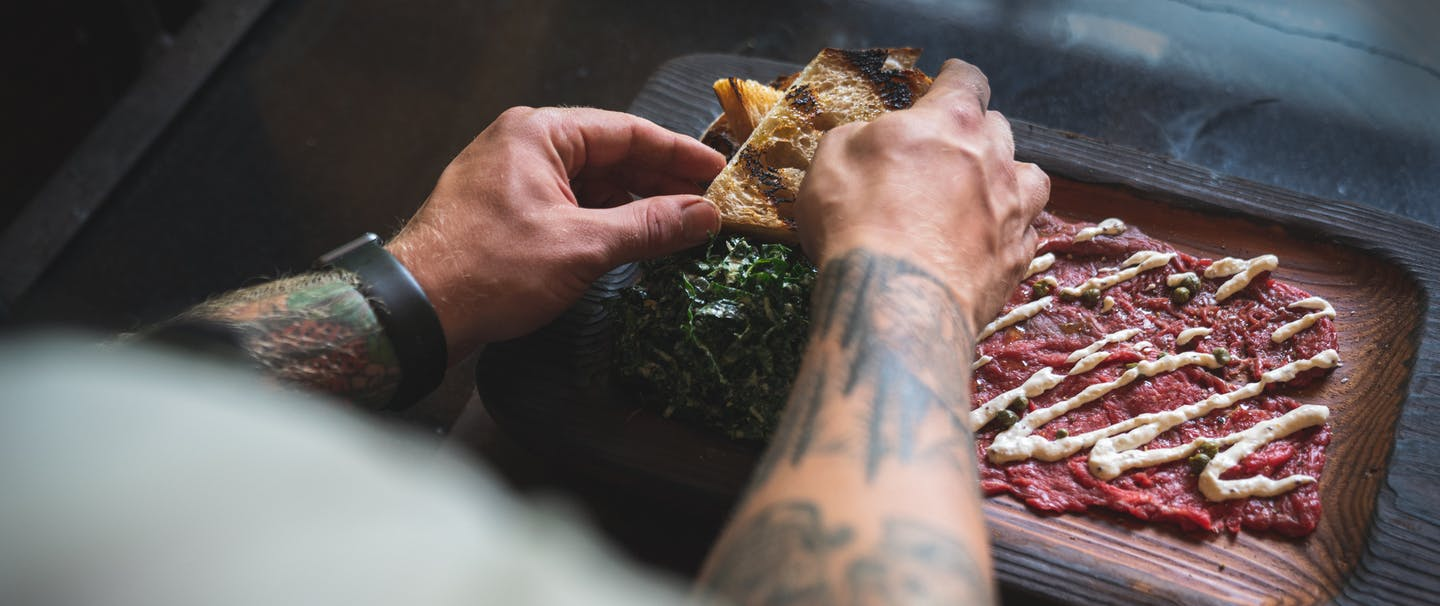 chef plating the dish with the final touches of drizzled with horseradish sauce, a side of kale salad and grilled bread on a dark wood serving dish
