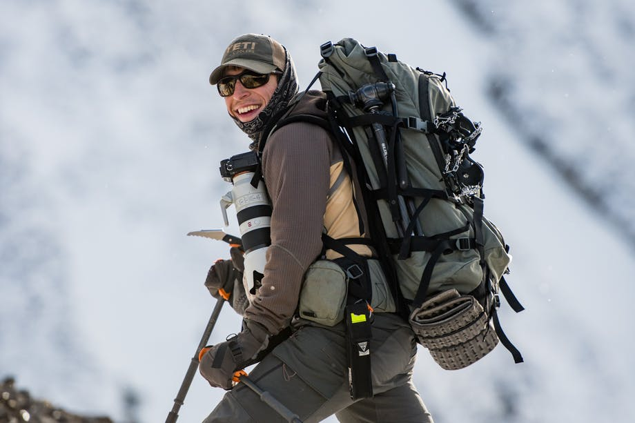 man wearing green hiking pack, dark green pants, shirt and cap, carrying a big camera and hiking poles up a snowy mountainside