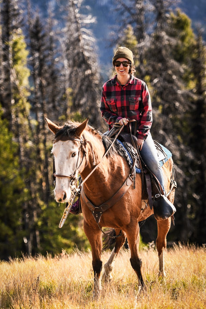 Frankie Foss wearing a winter hat, sunglasses and jeans riding a brown house in a field just outside of a wooded area