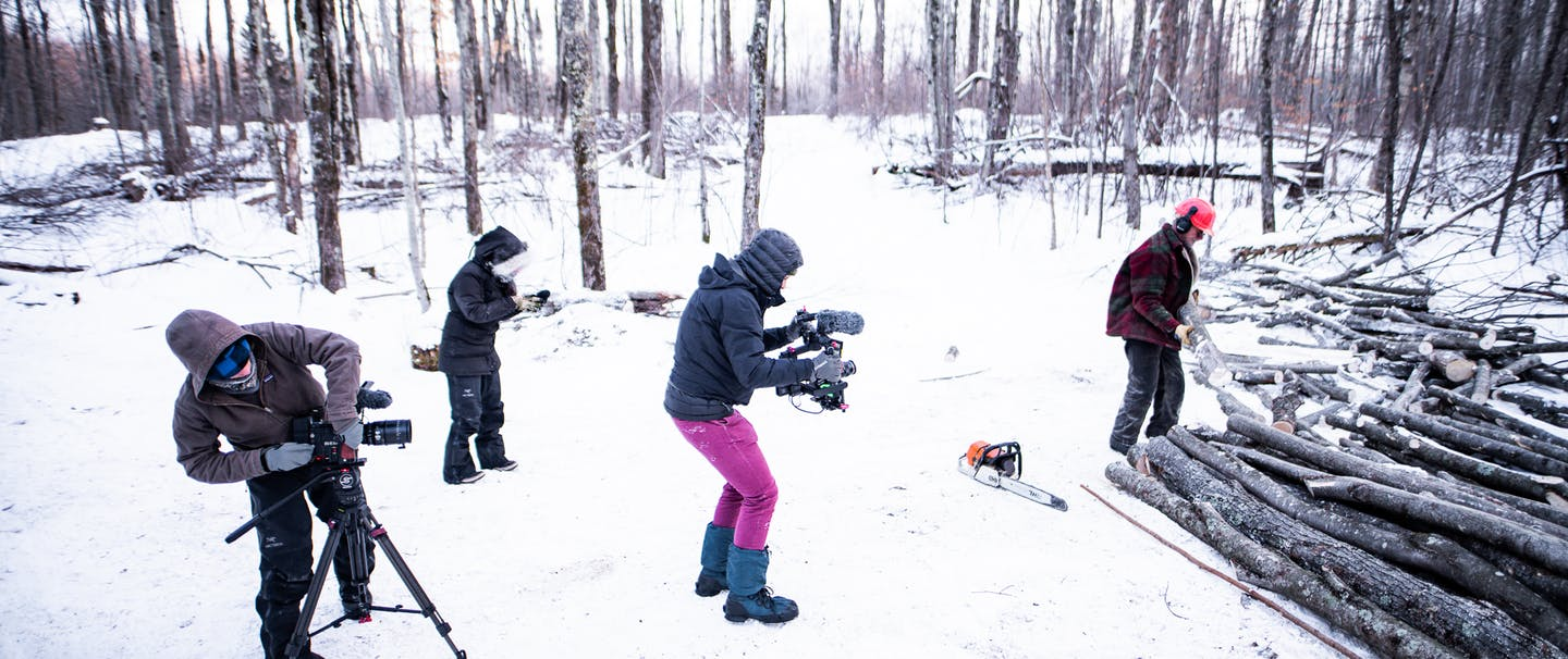 film crew on set, filming as Gary Edinger uses his chainsaw in the snowy winter woods