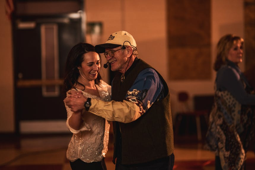 Frankie Foss, wearing a white shirt and her hair down, and Gary Edinger, wearing a white ball cap and a blue and white western shirt, square dancing as he calls the square dance