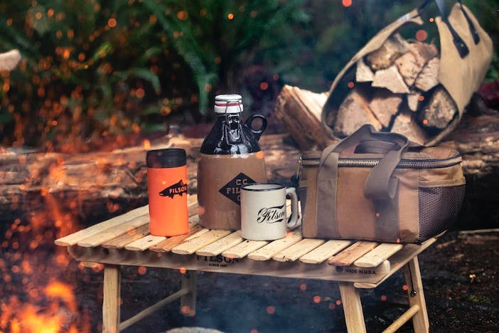 camping gear, orange mug, brown glass growler, cream ceramic mug, brown utility bag and a tan log carrier full of wood, in the woods next to a campfire