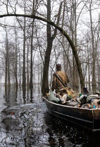 two hunters wearing camo walking through a swamp pulling a boat full of duck decoys