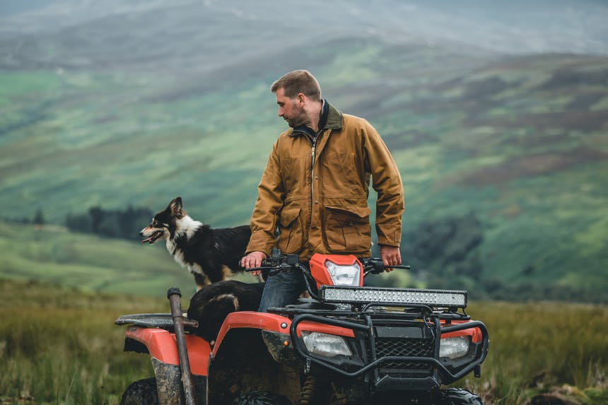 a brown, tan and white border collie sitting on the back of a red and black 4-wheeler driven by a man wearing a brown jacket standing and looking back to the dog