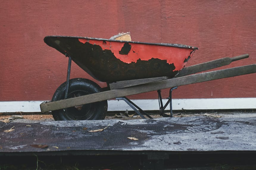 the side angle of a red wheel barrow with wood in it next to the base where it will be stacked in front of a red building