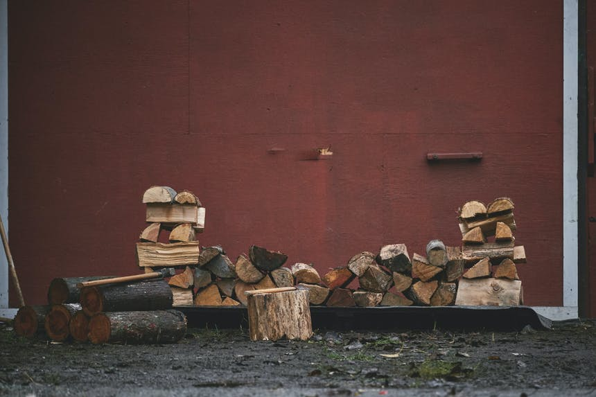 a wood pile with base and end posts secured in front of a red building