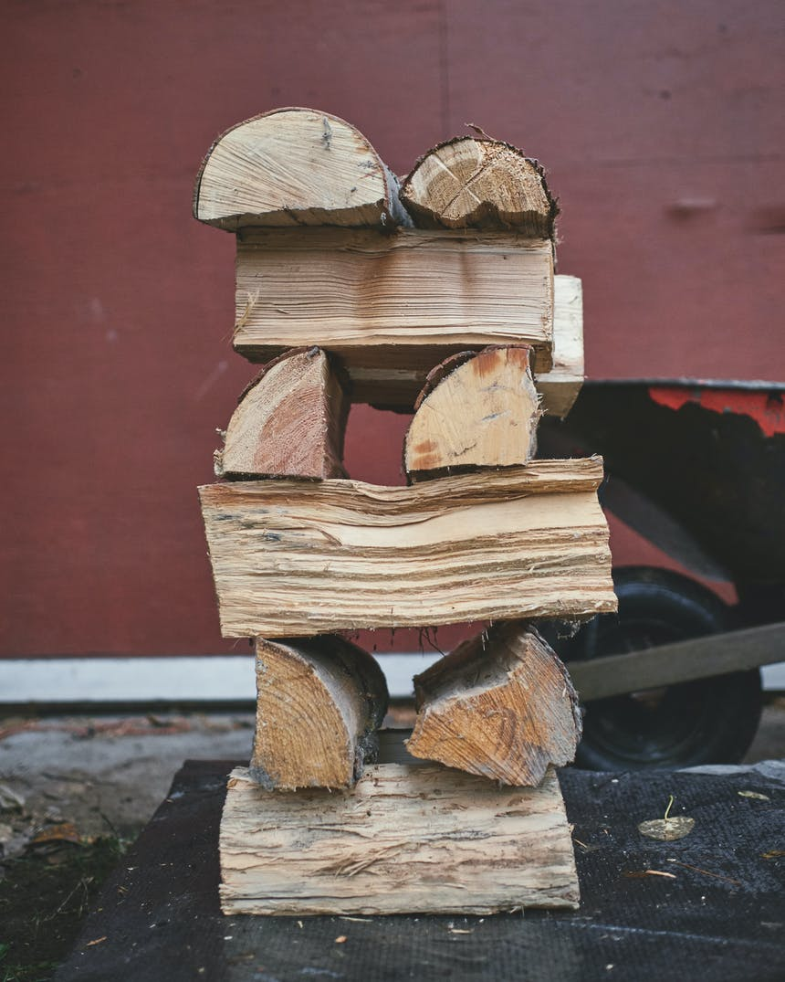 a stack of firewood with two pieces going one direction, while the next two are in the opposite direction, six pieces high with a red wheelbarrow and building behind it