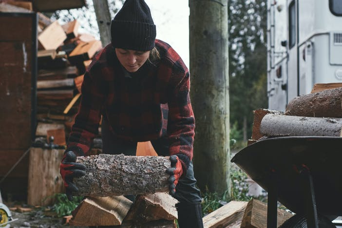 brunette woman wearing a black knit hat, red and black plaid sweater stacking firewood on a dark tarp