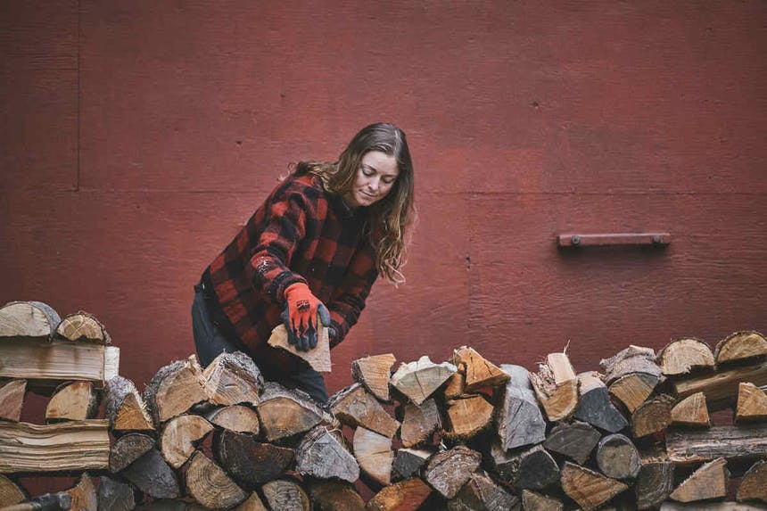 brunette woman wearing a red and black plaid sweater, black and orange gloves and dark pants stacking wood on a wood pile with a red building behind her