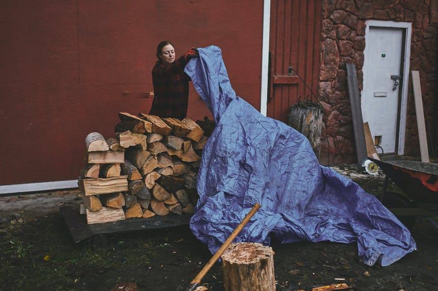 brunette women wearing a red and black plaid sweater pulling a faded blue tarp over the top of a stacked wood pile