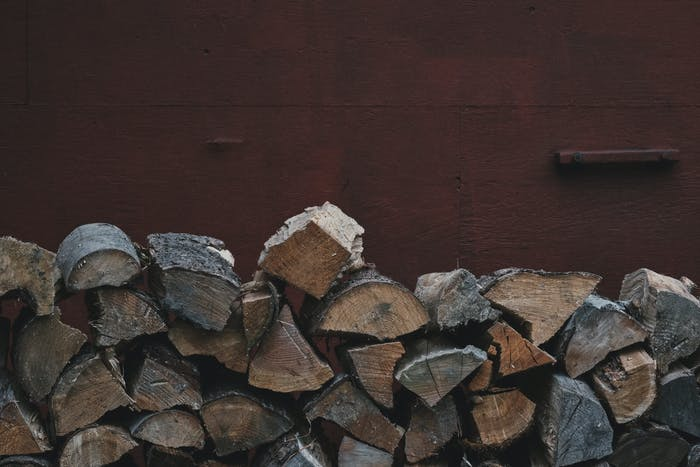 pile of split firewood stacked with a red building behind it