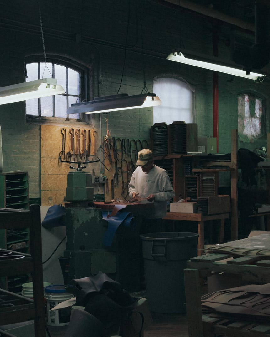 a man wearing a white sweatshirt and tan ball cap standing a worktable cutting out pieces of material with several tools hanging on the brick wall and shelves full of useful items in a dimly lit factory