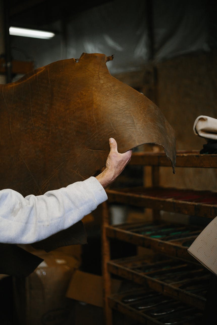 the right arm of a man wearing a long sleeve white sweatshirt moving a large piece of dark brown leather in a factory from one area to another