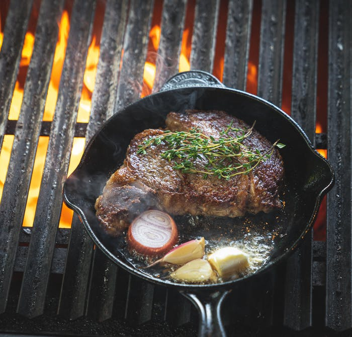 cast iron pan on a flaming outdoor grill with browned steak, halved red onion, whole garlic and sprigs of thyme