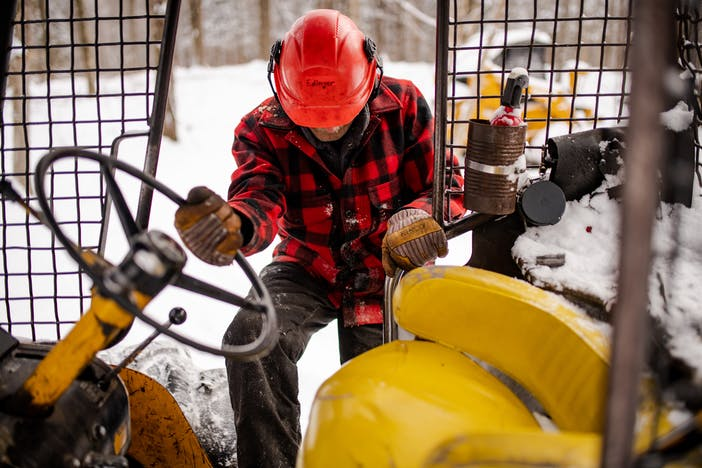 man wearing plaid red and black wool coat, snow pants and a orange hard hat climbing into a skid-steer with metal cage and yellow seat