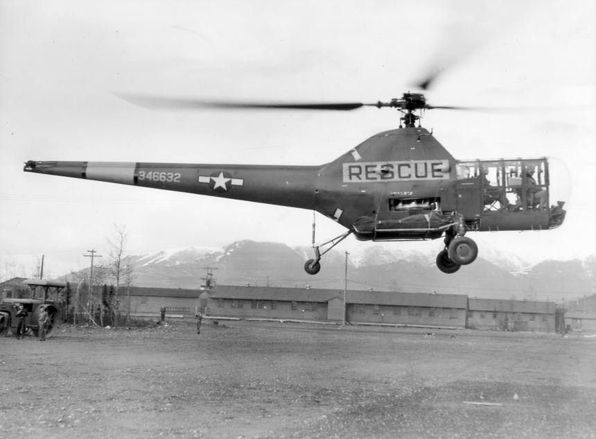 a historical black and white photo of the 10th rescue squadron helicopter taking off at Fort Richardson in Alaska in the early 1900s
