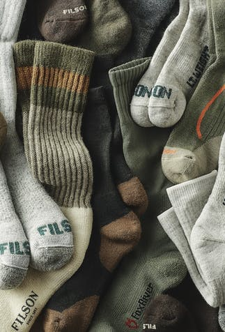 a close up of neatly laid out socks, six or more pairs of varying greens, browns and black with FILSON written on the top of the toes or bottom of the foot