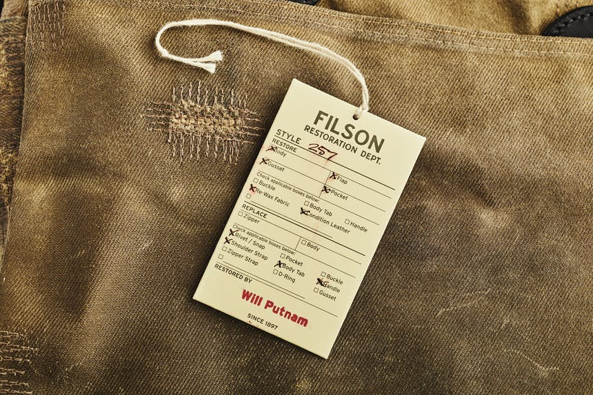 a close up image of a worn tan briefcase with extra stitching where it needed to be mended in a two spots and a Filson Restoration Department cream colored tag outlining the fixes the department resolved
