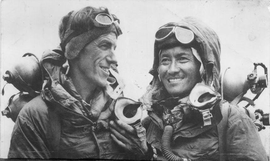 a black and white image of two mountaineering men with their googles on their foreheads, bundled up with jackets and wearing packs smiling from ear to ear
