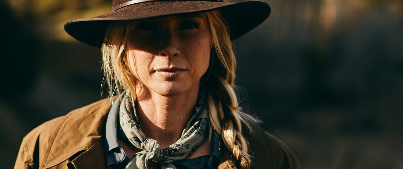 blonde woman with a long braid, grey scarf, brown cowboy hat and brown jacket with a blurry wooded background