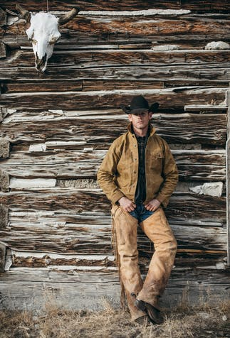 a man wearing a black cowboy hat, brown work jacket, jeans, chaps and cowboy boots leaning up against a wooden cabin with a bison skull in the top left corner