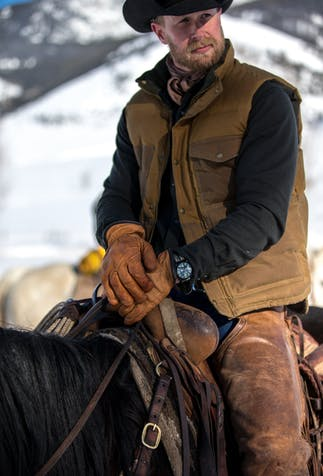 a close up image of a man wearing a black cowboy hat, brown vest, black long sleeve button up and chaps sitting in the saddle on his horse