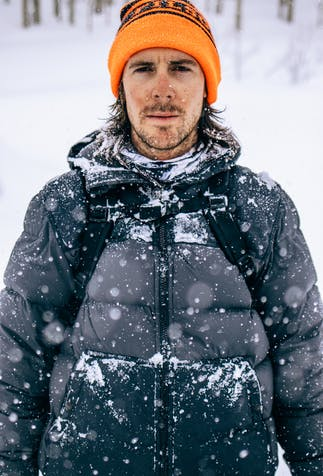 a man with a blaze orange beanie and dark grey down jacket with snow falling and collecting on his jacket and around his neck gaiter