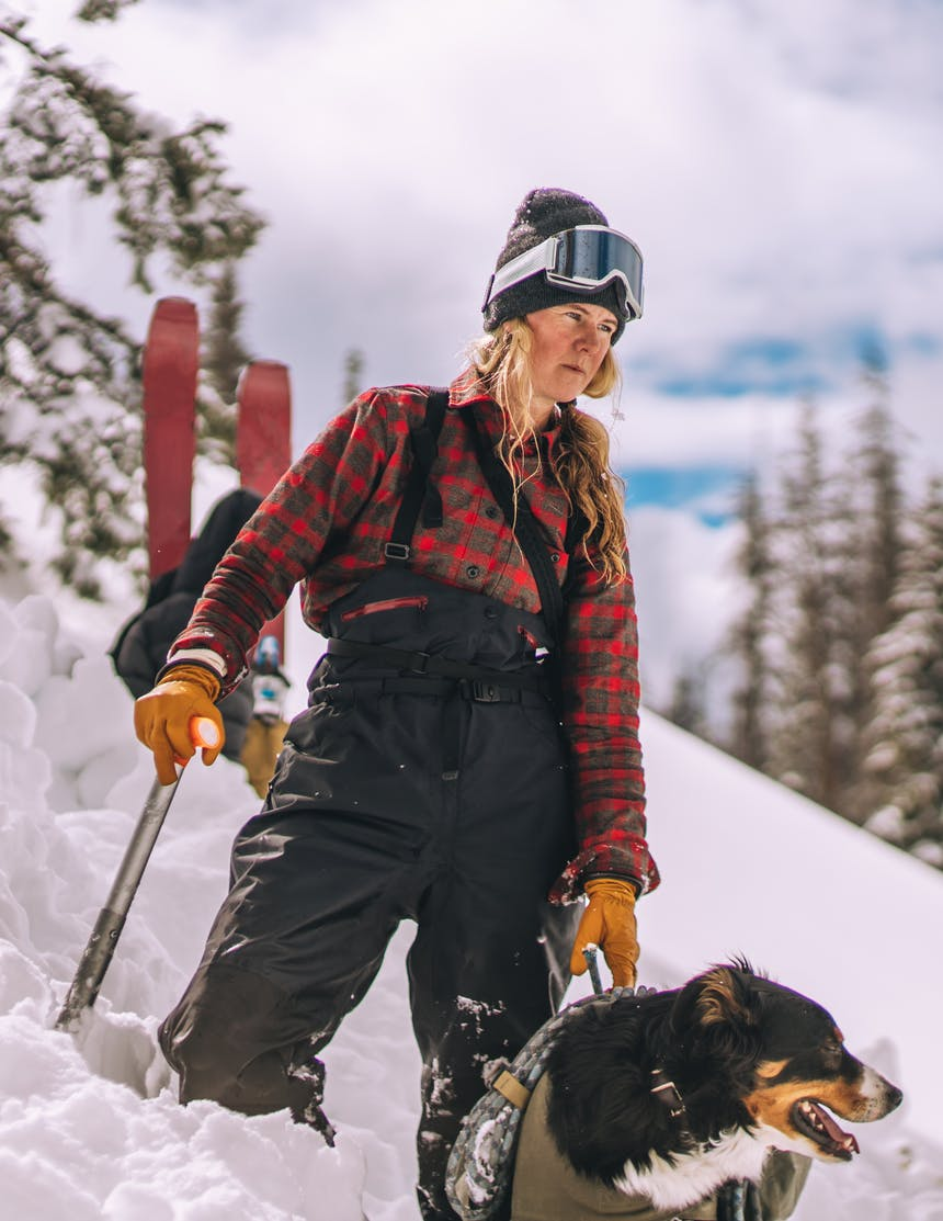 a blonde woman standing knee deep in snow wearing a brown and red flannel, grey beanie and black bib snow pants holding a shovel in the snow next to her black, brown and white dog wearing a pack holding gear and next to her red skies stuck in the snow behind them