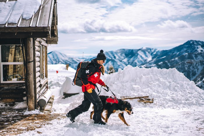 a blonde ski patroller wearing her red and black jacket with a white medical cross on the shoulder, black snow pants, black boots and holding the leash of her black, brown and white dog wearing his red and black rescue vest as they walk away from the chalet