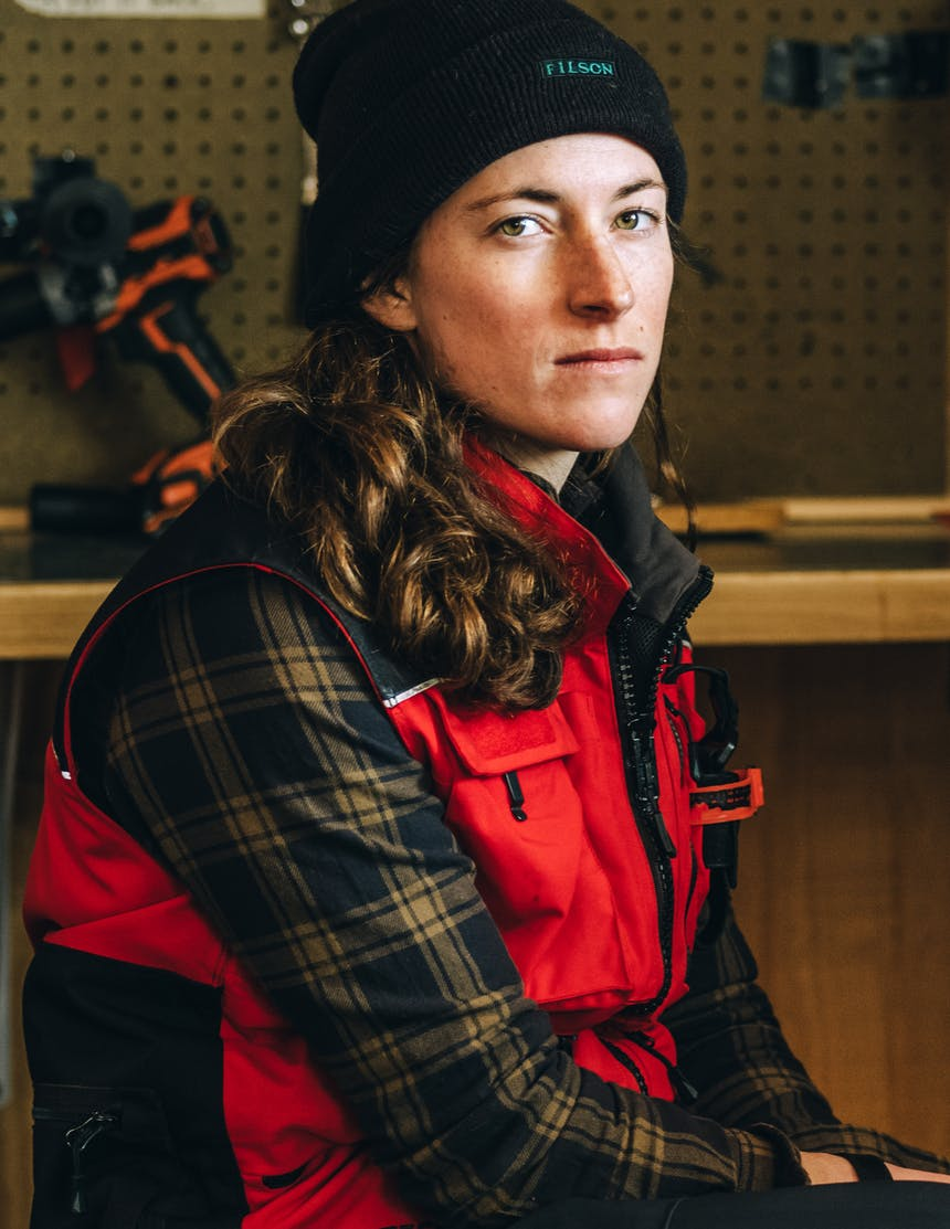 a brunette woman wearing a black beanie, red and black vest and brown and black plaid flannel sitting on a stool in a workshop glaring at the camera