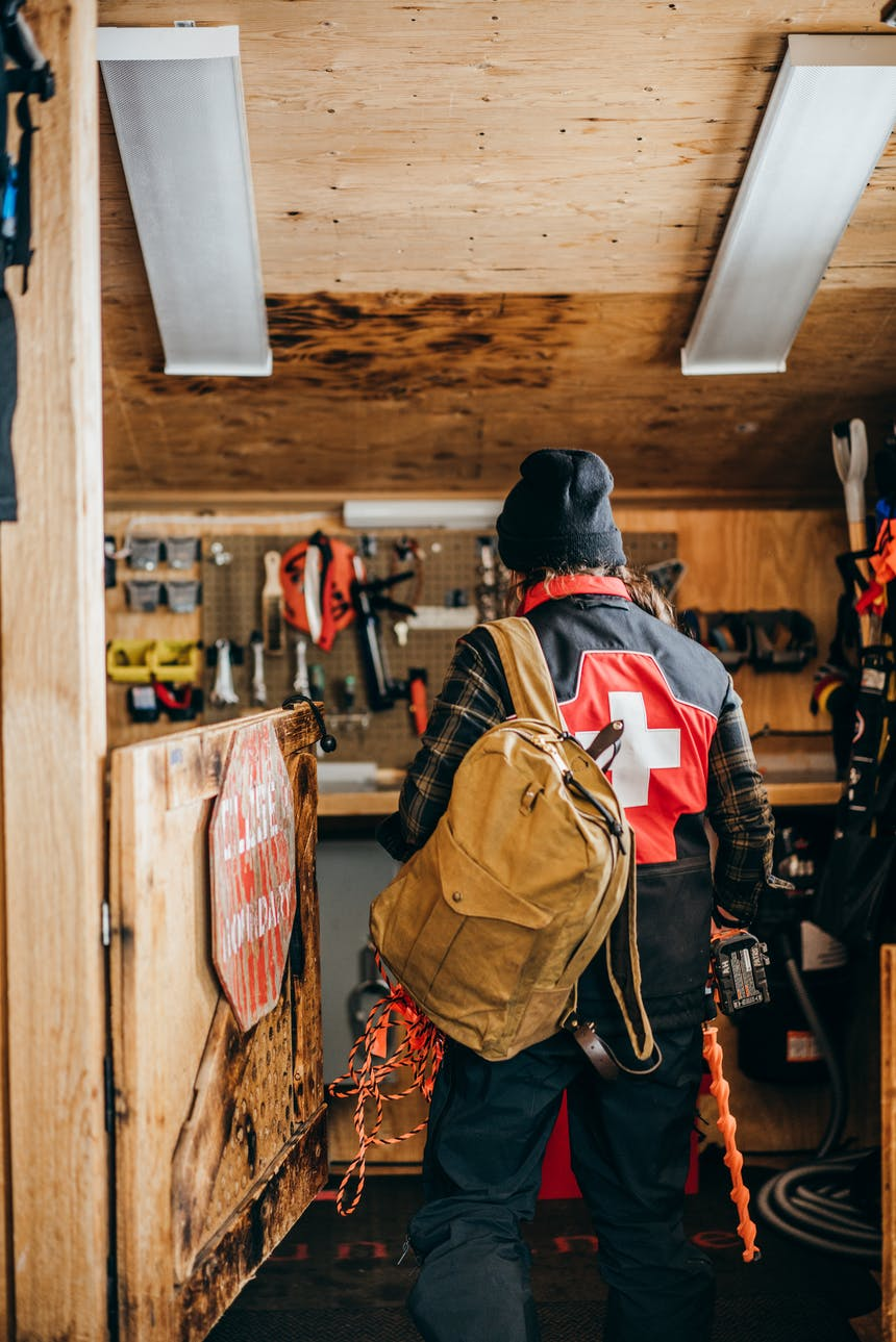 a ski patroller walking into the workshop of the chalet wearing a black beanie, red and black vest with a white medical cross on the back, black snow pants and holding a tan backpack on their left shoulder