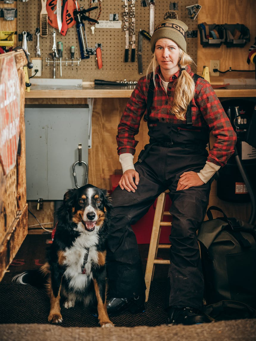 a blonde woman sitting on a wooden stool wearing a brown and red flannel, brown beanie with text FILSON and black bib snow pants and black boots next to her black, brown and white dog sitting with his tongue out in the workshop to the chalet